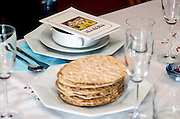 Matza and Haggada for pesach on the table set for a Jewish Festive meal on Passover