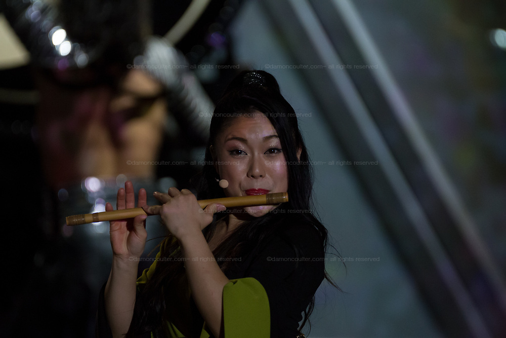 A performer plays a flute during a Mangekyo performance by Wadaiko group, DRUM TAO in Lumine 0 theatre, Shinjuku, Tokyo, Japan, Friday November 16th 2018. The Mangekyo  performance includes koto and shamisen music along with traditional  and contemporary taiko drumming and acrobatics. Organised by the Japan Tourist bureau (JTB) and the Japanese Government to entertain foreign visitors in readiness for the 2020 Tokyo Olympics. the performances run to the end of November and utilise state of the art projection mapping by TeamLab.