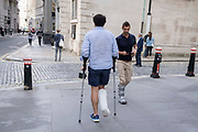 A man wearing a plaster cast and using mobility aids, hobbles past another male wearing a foot boot in the City of London, the capitals financial district, on 21st September 2021, in London, England.