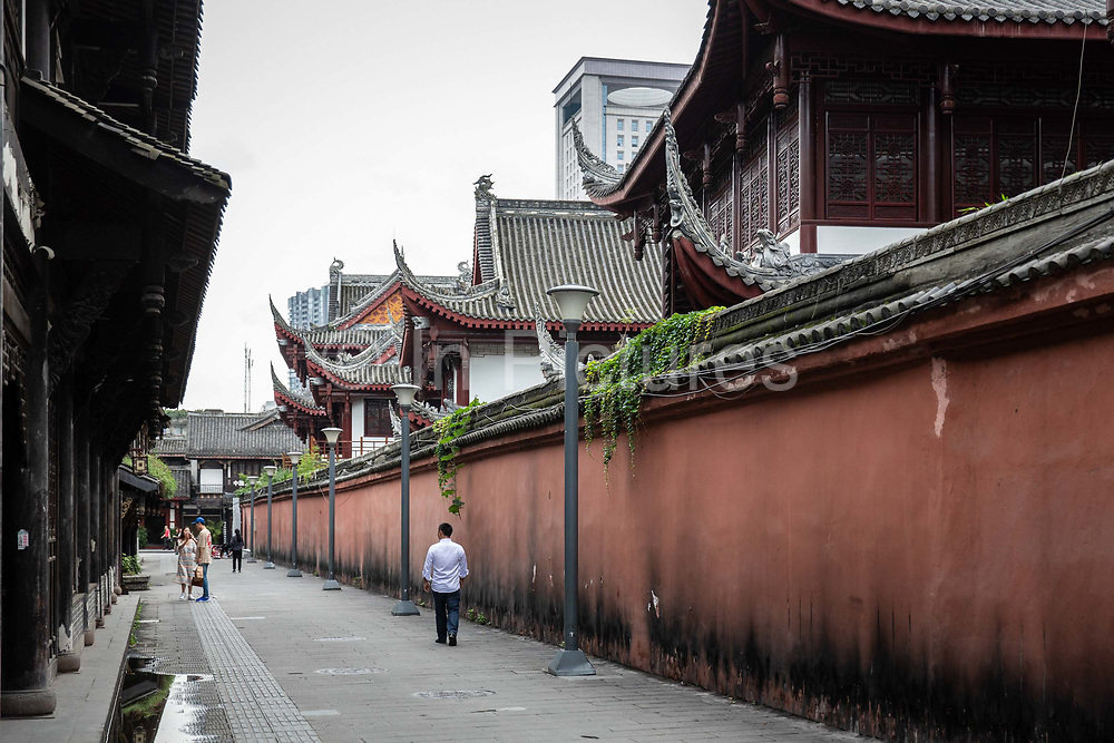 A man walks through an old neighbourhood restored for tourism in Chengdu, China, on Monday, Sept. 19, 2016. China faces unprecedented challenges as it restructures its economy away from old-line heavy manufacturing and toward consumption and services.