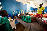 A wounded man is visited by relatives in the Boma hospital after being shot during and intertribal conflict.