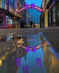 © Licensed to London News Pictures. 07/11/2020. London, UK. A reflection of Carnaby Street Christmas lights in a puddle of water. The installation will immerse Carnaby Street in pink neon lights, conveying the message of love, unity, and solidarity in these difficult times of the pandemic. The lights will be on display until January 5, 2021. Photo credit: Dinendra Haria/LNP