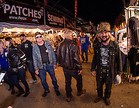 """Bruce Taylor (on right) the """"Medicine Man"""" walks through the Roadhouse vendors Friday evening.  Taylor has been coming to Bike Week since 1960. His first motorcycle was a 1947 Knucklehead Harley Davidson.   (Karen Bobotas/for the Laconia Daily Sun)"""