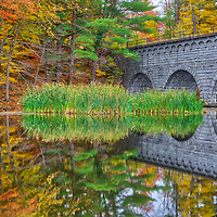 Massachusetts Wachusett Aqueduct and New England fall foliage reflecting in the Assabet River Reservoir in Northborough, MA on a beautiful autumn day. <br />