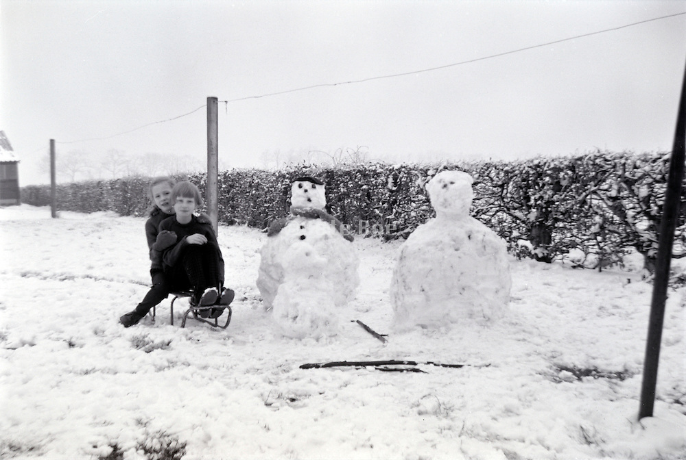 girls posing with their snowman 1960s