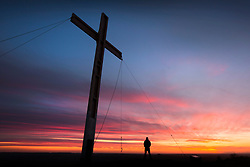 © Licensed to London News Pictures. 15/04/2017. Otley UK. A man watches the sunrise this morning in the shadow of the Easter cross that is placed on top of Otley Chevin in Yorkshire each year to celebrate Easter, the cross stands 32 ft tall & is made from wood salvaged from Manchester IRA bombing in 1996. Photo credit: Andrew McCaren/LNP