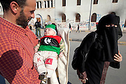 Mcc0030300 . Sunday Telegraph..Parents proudly show off their baby wearing the traditional Libyan colours (and rebel flag) in the rebel held city of Benghazi...Benghazi 25 March 2011