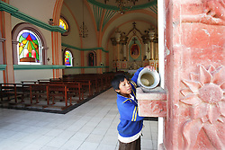 """A boy adds holy water before mass  at at church that Father Sebastian Obermaier built in El Alto, Bolivia. a town he has lived in for 27 years .  """"I don't feel Bolivian, I feel Aymara"""" he says, referring to the Aymara indigenous population that makes up more than 80% of El Alto. Father Obermaier has been designing and building churches in El Alto for the past 10 years, with a goal of building one church for every 10,000 inhabitants of the city, which currently has nearly 700,000 people living in it.  Everyone that visits Bolivia can see his numerous churches from the window of their airplane as it lands in El Alto.  The churches are marked by a style unique to Father Obermaier, that mixes indigenous symbols with tall towers and bright colors, that leave every church looking different, as if they were straight out of a children's pop-up book."""