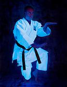 Man with black belt karate  outfit practicing Neko-Ashi-Dachi.Black light