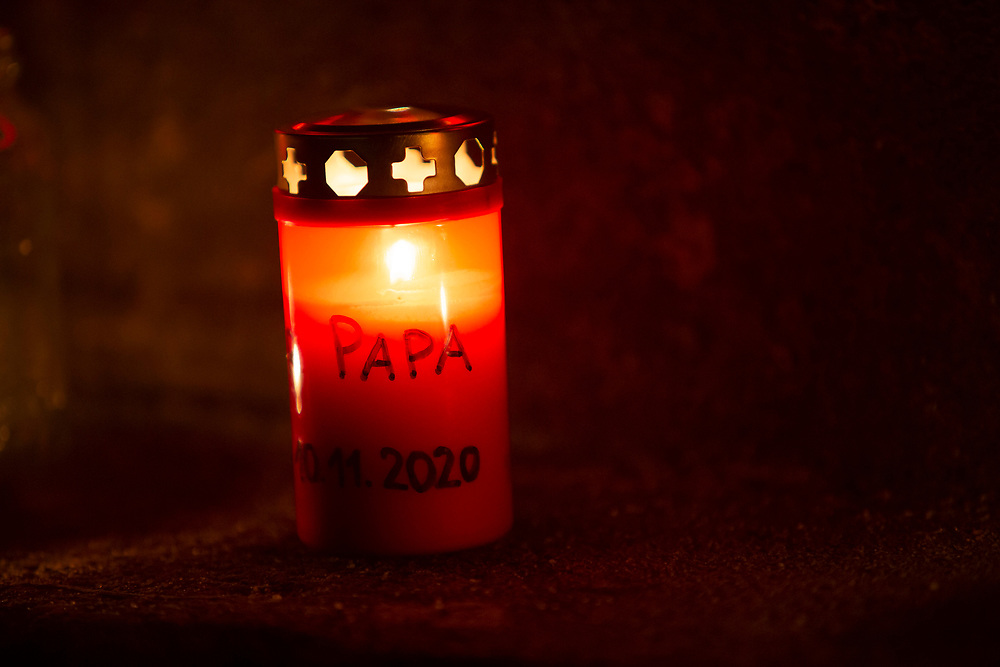 "A candle with the word ""PAPA"" written on it burns at a makeshift memorial in Berlin, Germany, January 17,  2021. The memorial is part of the initiative  ""Corona-Tote sichtbar machen"" (lit. Make corona deaths visible) by Christian Y. Schmidt and Veronika Radulovic,  since December 6, 2020, people gather at the fountain of Arnswalder Platz every Sunday at 16:00, light candles and place placards with the current death toll reported in Germany at the time. The death toll in Germany by variouse sources revolved around 47,000."