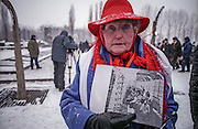 Eva Moses Kor, a survivor of the Auschwitz Nazi concentration camp, attending the ceremony to mark the 60th anniversary of its liberation. She is holding a photograph of herself and her twin sister Miriam taken by the Soviets after the liberation of the camp. On the selection platform at Auschwitz, the girls were identified as twins and earmarked for Dr. Josef Mengele's medical experiments.