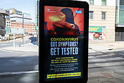HM Government, and NHS advertising boards advice to get tested if you have symptoms in Birmingham city centre which has very few people around due to the Coronavirus outbreak on 20th May 2020 in Birmingham, England, United Kingdom. Coronavirus or Covid-19 is a new respiratory illness that has not previously been seen in humans. While much or Europe has been placed into lockdown, the UK government has put in place more stringent rules as part of their long term strategy, and in particular social distancing.