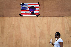 "© Licensed to London News Pictures. 13/06/2020. WATFORD, UK.  A woman walks by a sign on construction hoarding bearing the text ""I Can't Breathe"" in Watford High Street, north west London.  The sign references the death of George Floyd, an unarmed black man, who died whilst being arrested by police in Minneapolis, USA, in May.  His death has brought a renewed focus to the issue of racism and police brutality, including Black Lives Matter protests in cities across the world.  Photo credit: Stephen Chung/LNP"