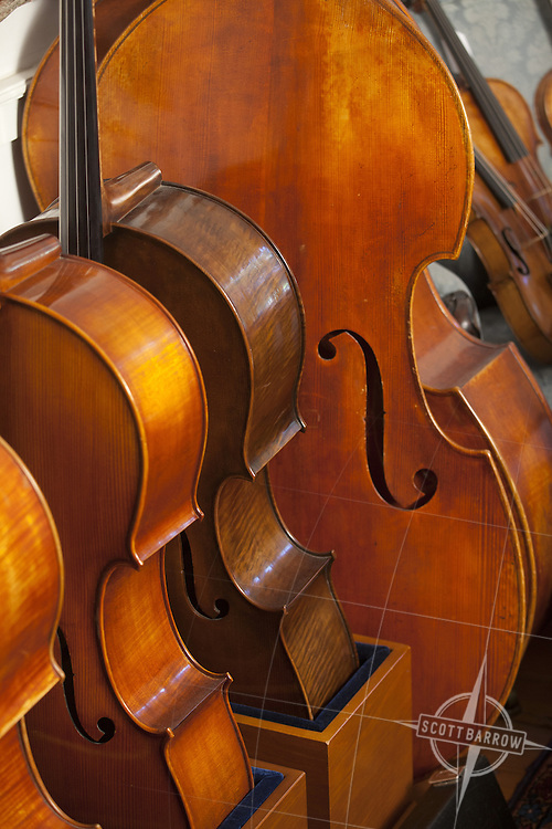 Cellos and a base fiddle for sale.