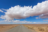 Road with desert landscape and cloudy blue sky in the Sahara desert of Morocco.