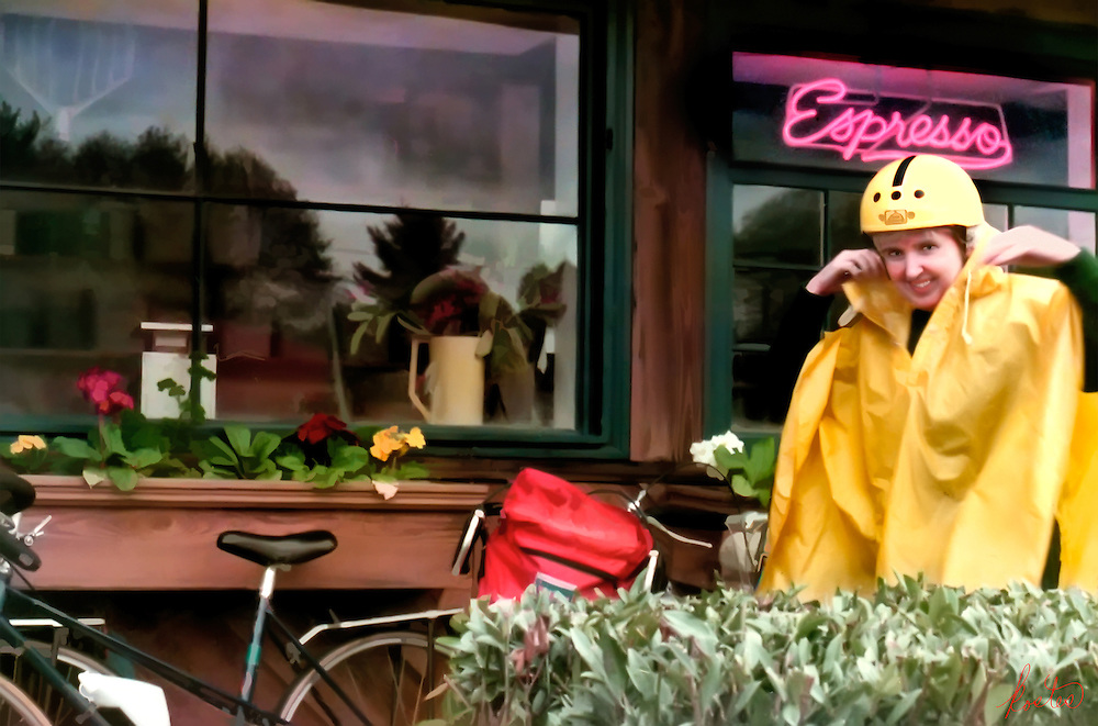 Bicycle rider in yellow rain slicker outside a coffee shop/bakery.
