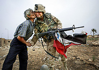 Baghdad, IRAQ -- 4/19/03 -- Army 422nd Civil Affairs Battalion (CA TEAM 1) SPC Yancey Christopher, 36 of Haw River, NC on a recon patrol with CA Team 1 carrying a discarded Iraqi flag id kissed on the cheeks by an Iraqi. -- Photo by Jack Gruber, USA TODAY