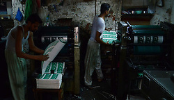 July 13, 2017 - Lahore, Punjab, Pakistan - Pakistani workers busy printing the national flag buntings in connection with upcoming Independence Day celebration in Lahore . As the nation starts preparing to celebrate the Independence Day of Pakistan in befitting manners, printing presses are busy day and night to print the items that are in great demand. Besides, vehicles could be seen on roads painted with national flag colors, which shows the enthusiasm of the people to commemorate the country's Independence Day. (Credit Image: © Rana Sajid Hussain/Pacific Press via ZUMA Wire)