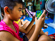 20 MAY 2017 - BANGKOK, THAILAND: Boys play video games on their smart phones in a home in Pom Mahakan. The final evictions of the remaining families in Pom Mahakan, a slum community in a 19th century fort in Bangkok, have started. City officials are moving the residents out of the fort. NGOs and historic preservation organizations protested the city's action but city officials did not relent and started evicting the remaining families in early March.        PHOTO BY JACK KURTZ