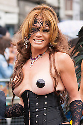 London, June 28th 2014. A topless reveler poses for the camera as the Pride London parade proceeds through the city's streets.
