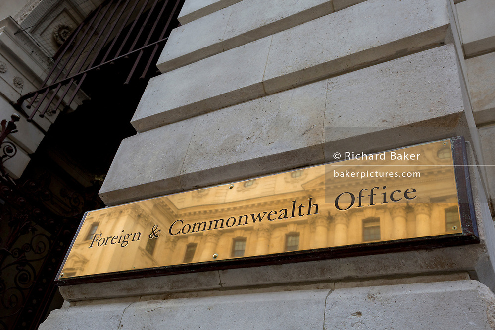 Detail of the brass nameplate outside the Foreign & Commonwealth Office outside the government department on King Charles Street SW1, on 5th October, 2017, in London, England. The main Foreign Office building is in King Charles Street, and was built by George Gilbert Scott in partnership with Matthew Digby Wyatt and completed in 1868 as part of the new block of government offices which included the India Office and later (1875) the Colonial and Home Offices. George Gilbert Scott was responsible for the overall classical design of these offices but he had an amicable partnership with Wyatt, the India Office's Surveyor, who designed and built the interior of the India Office.