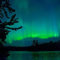 The Aurora Borealis glows over Lake of the Woods, Ontario, Canada.