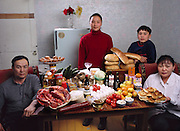 The Batsuuri family in their single-room home (a sublet in a bigger apartment) in Ulaanbaatar, Mongolia, with a week's worth of food. Standing behind Regzen Batsuuri, 44 (left), and Oyuntsetseg (Oyuna) Lhakamsuren, 38, are their children, Khorloo, 17, and Batbileg, 13. From the book Hungry Planet: What the World Eats (Model Released)