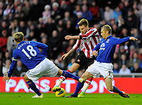 20111226: LONDON, UK - Barclays Premier League 2011/2012: Sunderland vs Everton.<br /> In photo: Nicklas Bendtner of Sunderland AFC (C) tries to get a shot past Phil Neville (L) and Leighton Baines of Everton FC (R).<br /> PHOTO: CITYFILES