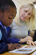 A young African school-girl reads a picture story book and is assisted by a volunteer teacher in a classroom in Prestwich Primary School, Green Point, Cape Town, South Africa. The teacher is a volunteer provided provided to the school by Shine Centre which is a charity that aims to address the high illiteracy rate in South Africa by improving literacy levels among children in schools and disadvantaged communities.