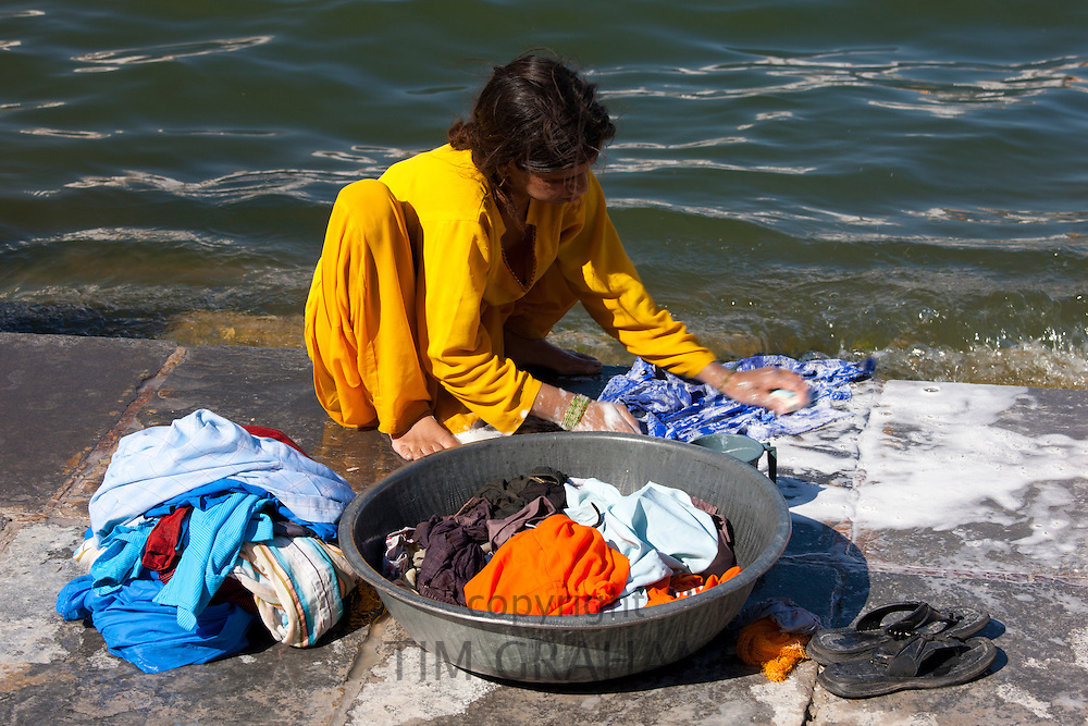 Young Indian girl squatting down to do her laundry in the waters of Lake Pichola, Udaipur, Rajasthan, Western India