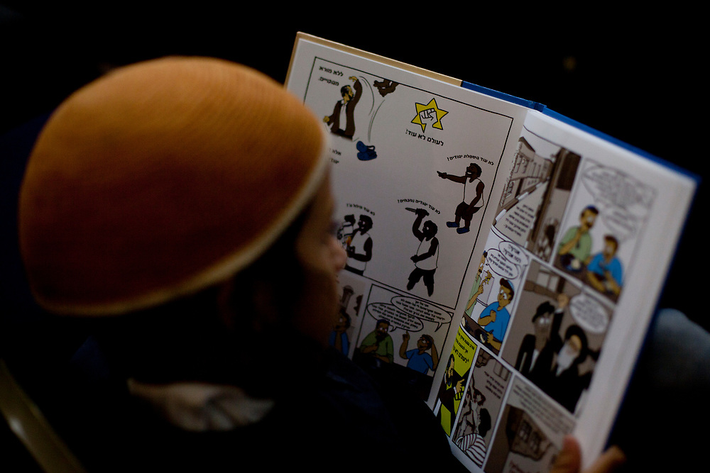"""A young Jewish boy reads a comic book honoring the late Rabbi Meir Kahane, founder of both the Jewish Defense League (JDL) and """"Kach"""", an Israeli political party, during a rally in Jerusalem on October 26, 2010, marking the 20th anniversary of his death after he was assassinated by an Arab gunman in a Manhattan hotel in November 1990."""