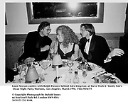 Liam Neeson confers with Ralph Fiennes behind Alex Kingston  at Steve Tisch &  Vanity Fair's Oscar Night Party,<br />