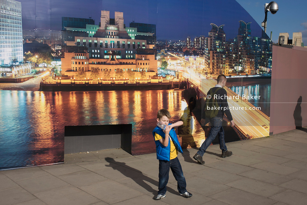 A young boy plays by a construction hoarding, a night time panorama of the Thames south bank, featuring the HQ of the intelligence service (MI6) across the river in Vauxhall.