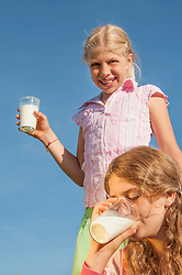 Two girls (10-11) (12-13) in field holding glass of milk, smiling, portrait, close-up
