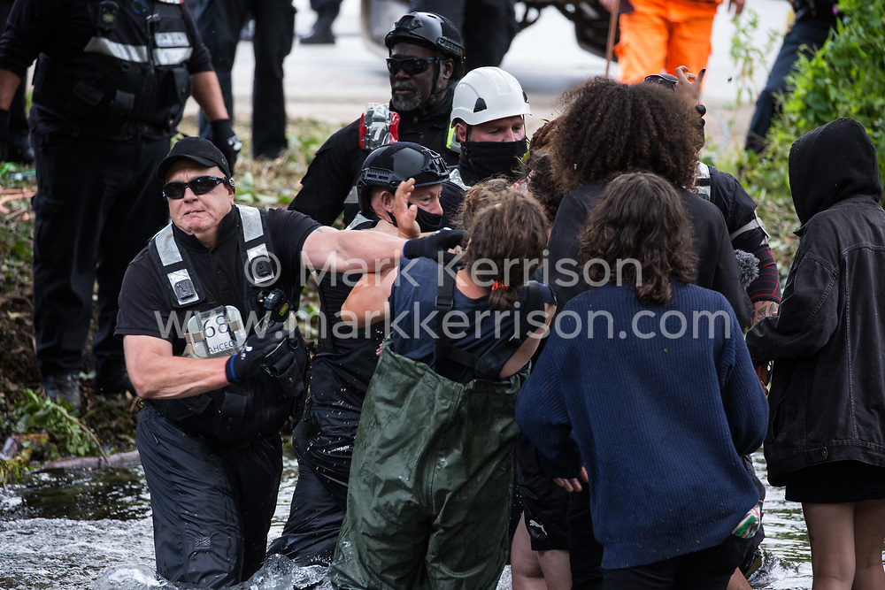 Denham, UK. 24 July, 2020. Enforcement agents from the National Eviction Team use force against environmental activists from HS2 Rebellion trying to protect an ancient alder tree from destruction in connection with works for the HS2 high-speed rail link in Denham Country Park. A large policing operation involving the Metropolitan Police, Thames Valley Police, City of London Police and Hampshire Police as well as the National Eviction Team was put in place to enable HS2 to remove the tree.