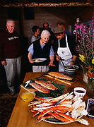 Chef Steve Lacroix serving seafood supper to Madeleine Kamman with Alan Kamma, Patty Park, Bob Griffin and Tom Dowd beyond, Winterlake Lodge seafood dinner, Alaska.   (MR)