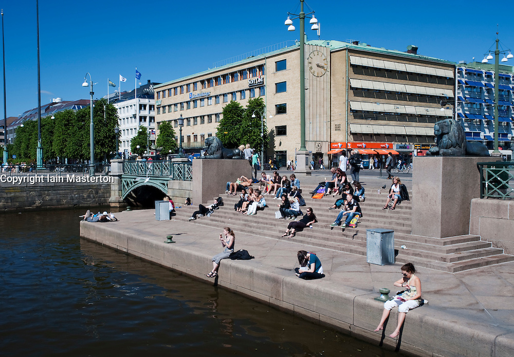 People sitting beside canal in central Gothenburg Sweden