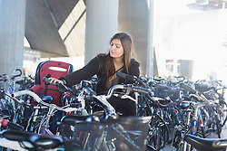 Young woman parking her bicycle, Freiburg im Breisgau, Baden-Württemberg, Germany