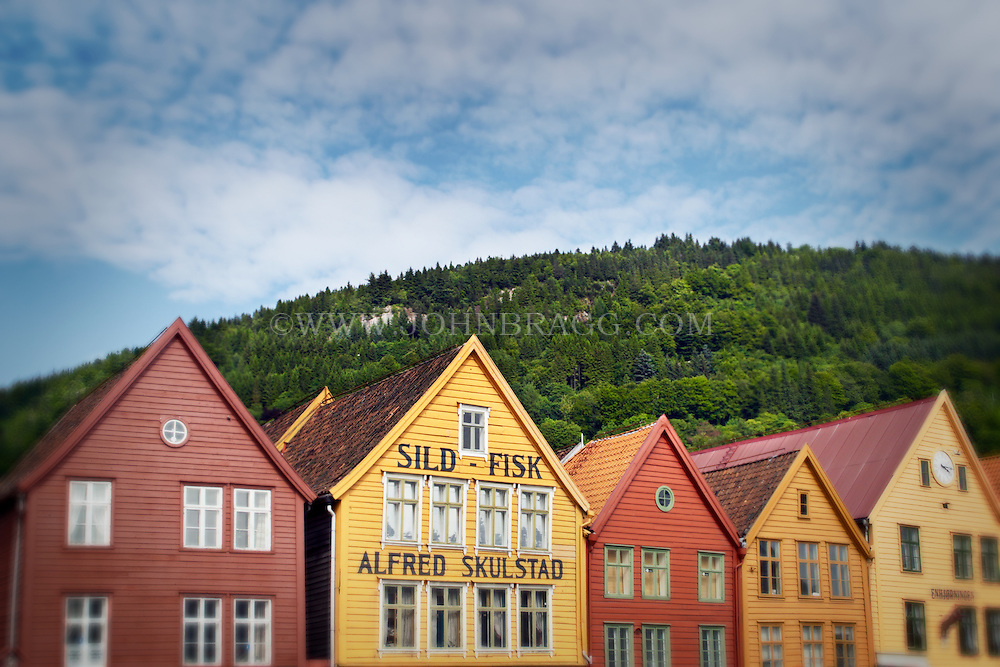 Colorful rooftops in old Bergen, Norway with mountains and a cloudy blue sky.