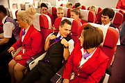 One week away from getting their 'wings' these flight attendants proudly wear their red uniforms as they undergo an in flight training session focussing on how to serve meals and using the service trolley. Virgin Atlantic air stewardess and steward training at The Base training facility in Crawley. Potential hostesses are put through a gruelling 6 week training program, during which they are tested to their limits. With exams every day requiring an 88% score to pass. The Base is a modern environment for a state of the art airline training situated next to Virgin Atlantic's HQ.
