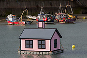 A floating pink bungalow in Folkestone harbour built by the artist Richard Woods as part of the 2017 Folkestone Triennial. Folkestone, Kent. The artist wanted to create a piece about the housing crisis in the UK.