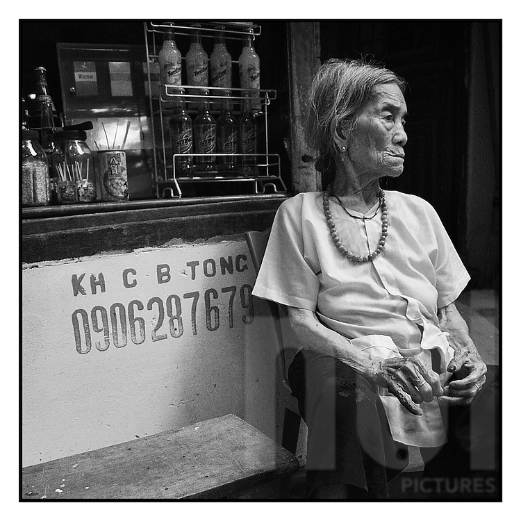 Portrait of a dreaming grand mother selling soda and waiting for some customers