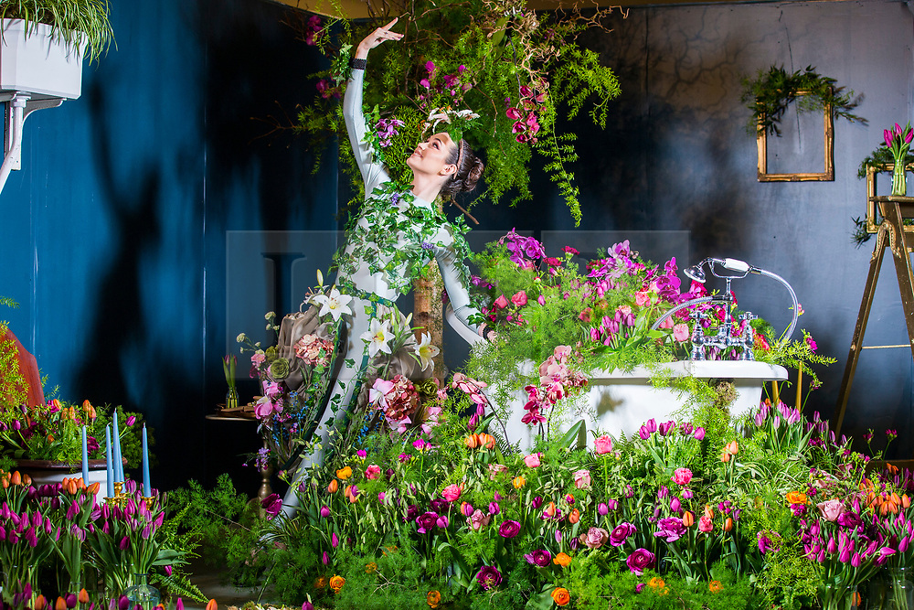 © Licensed to London News Pictures. 25/04/2018. Harrogate UK. Dancer Alison Parsons wears a flower dress in bathroom of the Green House display at this years Harrogate Flower Show in which starts tomorrow.  The GREENhouse has been designed to blur the lines between house and garden, creating a home infused with nature complete with living wallpaper,cascading flower shower, an aromatic bed of herbs and even a vege-table. Photo credit: Andrew McCaren/LNP