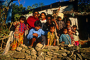 A Nepali family consisting of parents and young children are viewed outside their home in the central region of the Himalayan mountain kingdom. 8 children and 3 adults are near a dry stone wall in a foothill dwelling near the town of Gorkha where the British army traditionally find young men for the Gurkha regiment (as thay have done since 1857). The family are wearing clean clothes with bright colours and appear healthy despite this country - and especially for those living at altitude - being one of the world's poorest. The prospects for these children may mean they will in future try to seek work in the cities like Kathmandu rather than face a lifetime's struggle in local agriculture. Their supplies and contact with the outside world comes up from tracks of boulders and stone along which either men or yaks carry up food for basic survival and luxury goods.