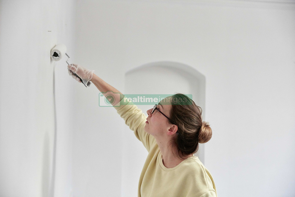 February 14, 2018 - Woman reaching up using roller to paint wall (Credit Image: © Mint Images via ZUMA Wire)
