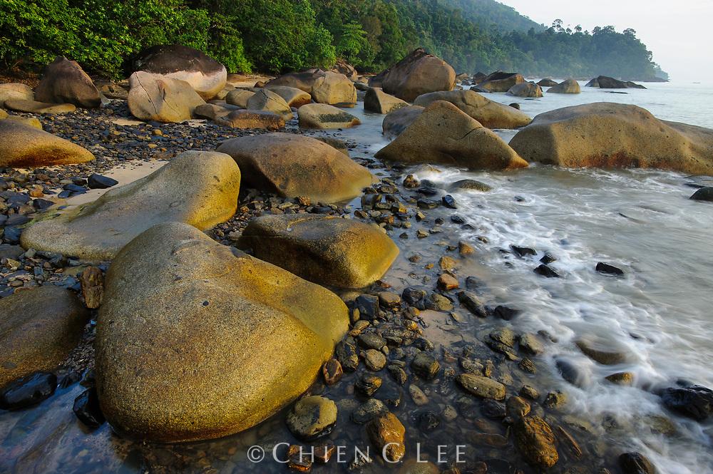 Large granite boulders decorate the coastline at Tanjung Datu National Park at the western tip of Borneo. Sarawak, Malaysia.