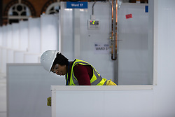 © Licensed to London News Pictures. 12/04/2020. Manchester, UK. Cleaner ISABEL INJAI (30) cleaning one of the hand washing terminals . The National Health Service is building a 648 bed field hospital for the treatment of Covid-19 patients , at the historical railway station terminus which now forms the main hall of the Manchester Central Convention Centre . The facility is due to open on Easter Monday , 13th April 2020 , and will treat patients from across the North West of England , providing them with general medical care and oxygen therapy after discharge from Intensive Care Units . Photo credit: Joel Goodman/LNP