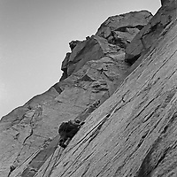 """Roger Schley ascends """"Cucumbers,"""" a difficult route on the north face of Cardinal Pinnacle in the Sierra Nevada above Bishop, California.  1973."""