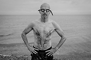 A portrait of a tired but fulfilled male sea swimmer who has just left the tidal waters after his swim several metres away from the beach on the Thames Estuary, on 25th July 2021, in Whitstable, England.