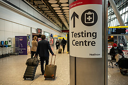 © Licensed to London News Pictures. 17/01/2021. London, UK. Passengers walk past a Testing Centre sign at London Heathrow.  Passengers arriving from abroad on Monday morning will have to show that they have had a negative Covid-19 test. Today, Foreign Secretary Dominic Rabb, said that lockdown could be lifted in March but with tier systems in place as health chiefs reveal that a 24/7 vaccination pilot will begin next week as total Covid-19 deaths reach over 88,000 this weekend. Photo credit: Alex Lentati/LNP